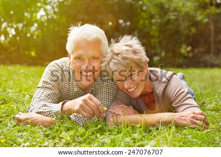 Happy senior couple laying in meadow in the grass in summer - stock photo