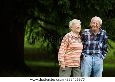 Happy senior couple looking at camera and laughing, Senior woman hugging her partner on a sunny day, Smiling Caucasian older couple embracing, blurry background - stock photo