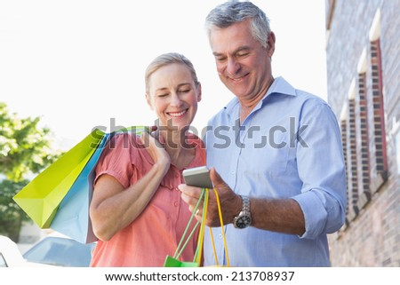 Happy senior couple looking at smartphone holding shopping bags on a sunny day - stock photo