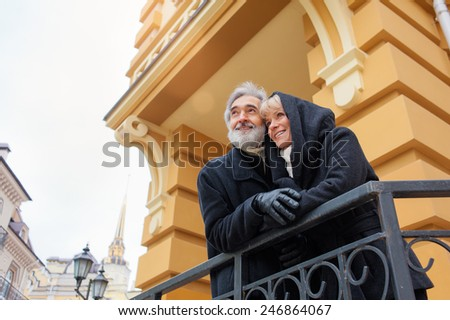 Happy senior couple, man and wife, traveling around Europe, enjoying beautiful old buildings in city - active retirement concept - stock photo