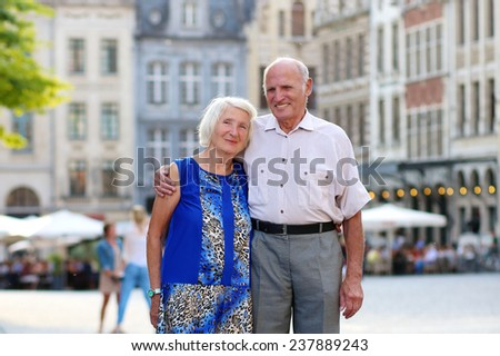 Happy senior couple, man and wife, traveling around Europe, enjoying beautiful old square in city of Leuven, Belgium - active retirement concept - stock photo