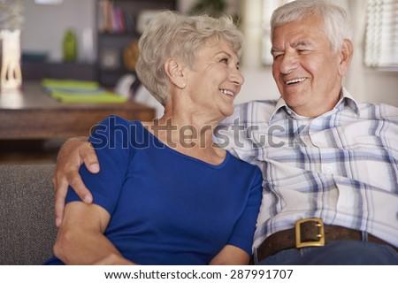 Happy senior couple on te sofa - stock photo