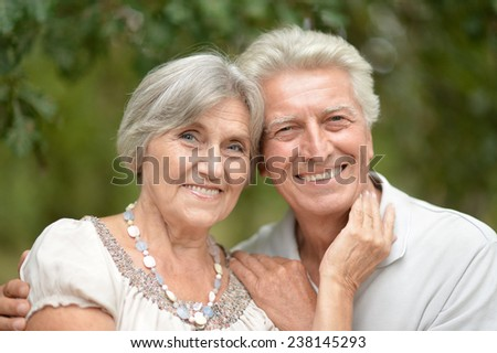 Happy senior couple on the veranda,reading a book - stock photo