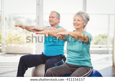 Happy senior couple performing exercise while sitting on exercise ball at home - stock photo