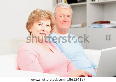 Happy senior couple planning for retirement at home. They surfing on internet with laptop - stock photo