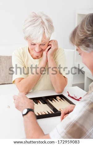 Happy Senior Couple Playing Game Of Backgammon At Home - stock photo