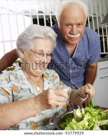 Happy senior couple preparing vegetable salad in the kitchen. Grandparents at kitchen preparing vegetable salad. - stock photo
