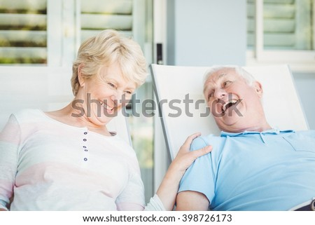 Happy senior couple relaxing on lounge chair at porch - stock photo