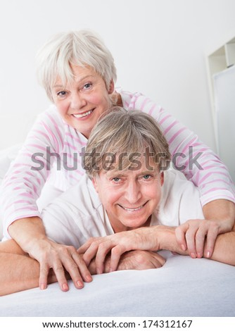 Happy Senior Couple Relaxing On Sofa At Home - stock photo