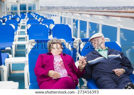 Happy Senior Couple Relaxing On The Deck of a Luxury Passenger Cruise Ship. - stock photo