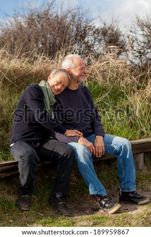 happy senior couple relaxing together in the sunshine on a wooden bench in the countryside with the one reclining full length on the seat with his head on his partners lap - stock photo