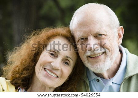 Happy Senior Couple Resting Heads on Each Other Outdoors in a Park - stock photo