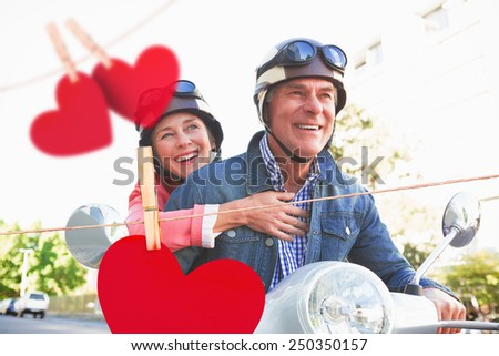 Happy senior couple riding a moped against hearts hanging on a line - stock photo