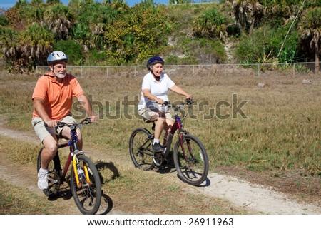 Happy senior couple riding their bikes through the park. - stock photo