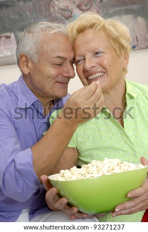 happy senior couple sharing and eating popcorn. - stock photo