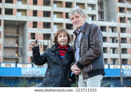 Happy senior couple showing house keys standing against building under construction - stock photo