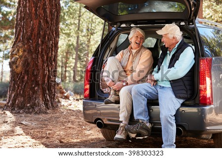 Happy senior couple sit in open car trunk preparing for hike - stock photo