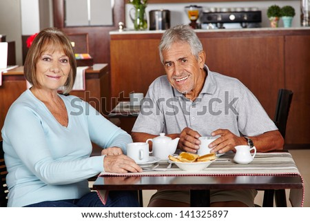 Happy senior couple sitting at breakfast in a hotel - stock photo