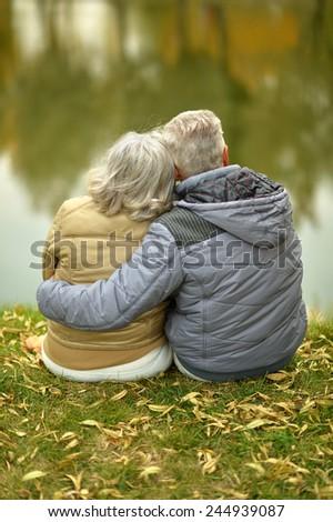 Happy senior couple sitting in autumn near lake - stock photo