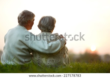 Happy senior couple sitting in autumn park - stock photo