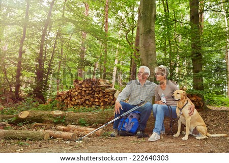 Happy senior couple sitting in forest with dog in summer - stock photo