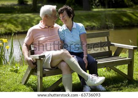 Happy senior couple sitting on a bench - stock photo
