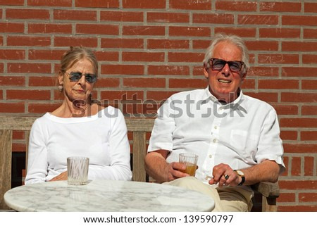 Happy senior couple sitting outdoors in garden enjoying fruit juice. - stock photo