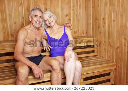 Happy senior couple sitting together in a sauna in their holidays - stock photo