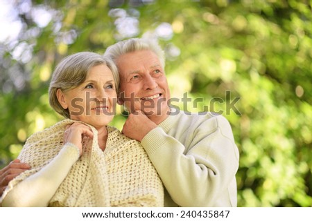 Happy senior couple standing in autumn park - stock photo