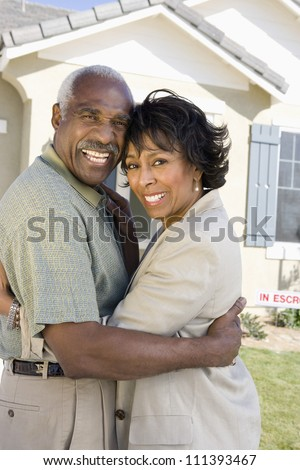 Happy senior couple standing in front of house for sale - stock photo