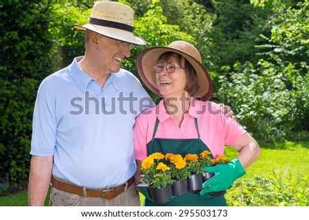 Happy Senior Couple Standing in Garden Looking at Each Other Holding Flats of Bright Orange Flowers for Planting - stock photo