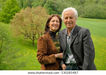 Happy senior couple standing on a meadow, enjoying themselves and smiling into the camera - stock photo