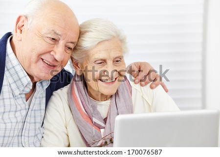 Happy senior couple surfing the internet with laptop computer - stock photo