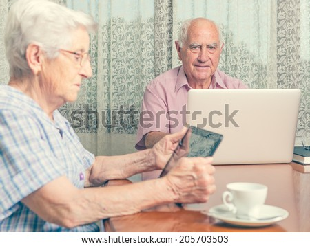 Happy senior couple surfing the internet with laptop computer and tablet - stock photo
