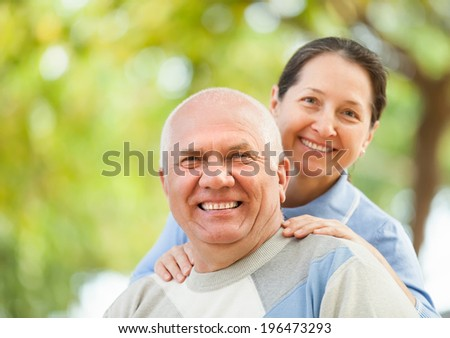 Happy senior couple together in autumn park against blured trees - stock photo