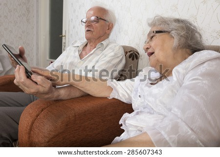 Happy senior couple using a tablet. Technology used by elders - stock photo