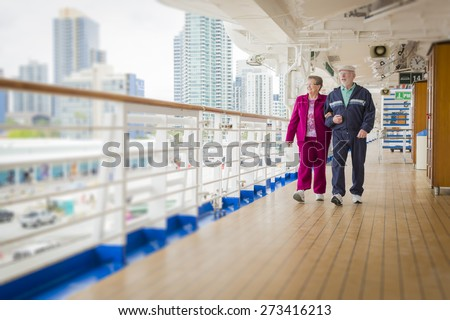 Happy Senior Couple Walking The Deck of a Luxury Passenger Cruise Ship. - stock photo