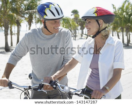 Happy senior couple wearing helmets with bicycles on tropical beach - stock photo
