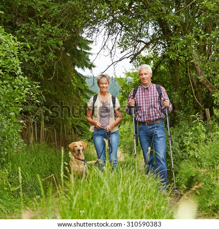 Happy senior couple with dog on a hike in summer in the nature - stock photo