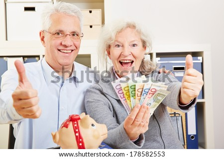 Happy senior couple with fan of Euro money holding thumbs up - stock photo