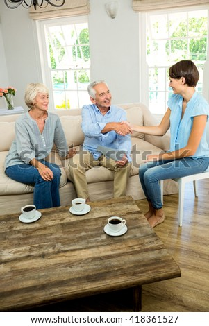 Happy senior couple with female consultant sitting on sofa at home - stock photo