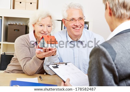 Happy senior couple with little house buying real eastate in office - stock photo