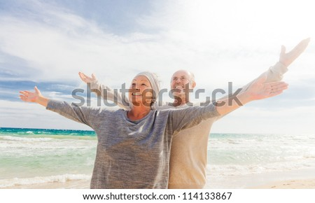 happy senior couple with outstretched arms enjoying retirement - stock photo