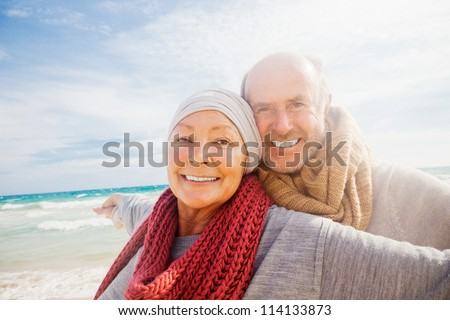 happy senior couple with outstretched arms enjoying retirement flying - stock photo