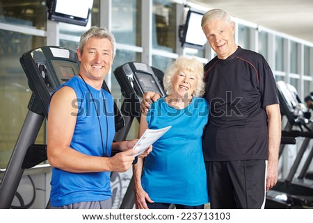Happy senior couple with personal trainer in fitness center at treadmill - stock photo