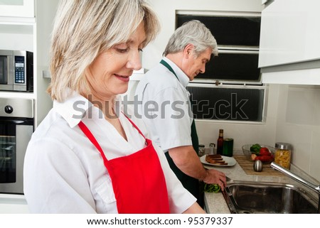 Happy senior couple working together in the kitchen - stock photo