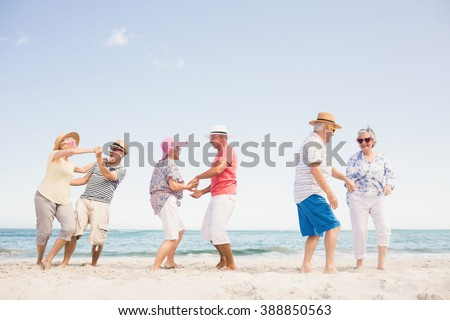 Happy senior couples dancing on the beach - stock photo