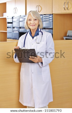Happy senior doctor with clipboard at hospital reception - stock photo