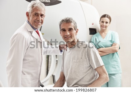 Happy senior doctor with his male patient at CT scanner machine. Female assistant on background. - stock photo