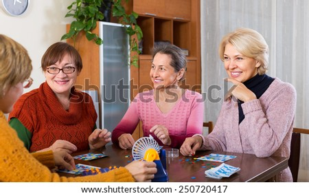 Happy senior female friends having fun with table game indoor  - stock photo